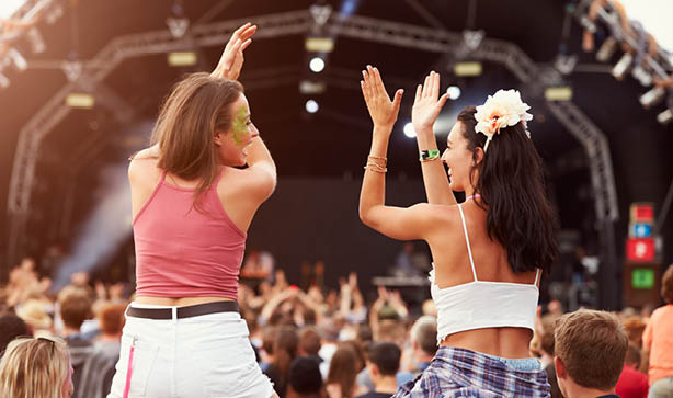 Two women showing their festival fashion off while cheering in the crowd