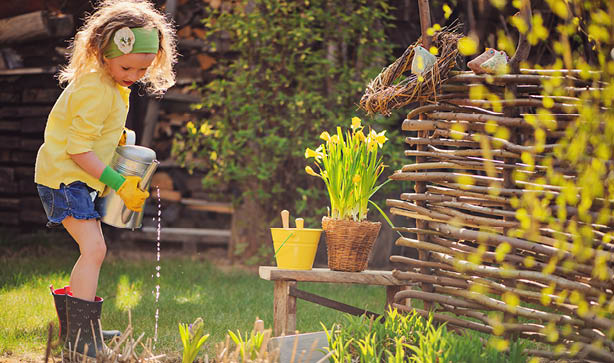 A little blonde girl watering the garden