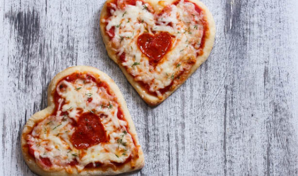 Two heart shaped pizzas on a wooden table