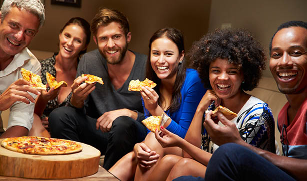 Friends sitting together eating pizza and watching a football match