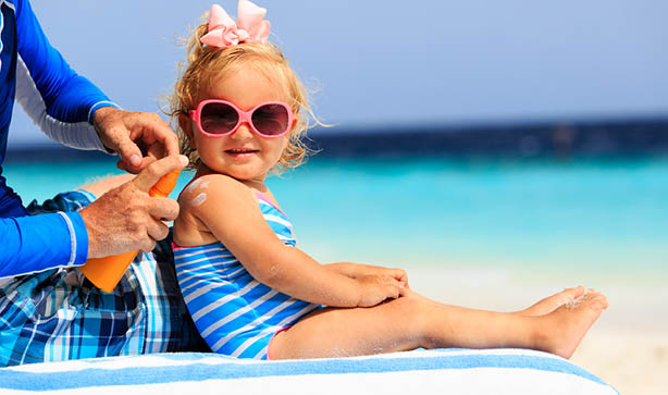 A little girl smiling wearing sunglasses and swim wear on the beach getting sun lotion applied by her parent