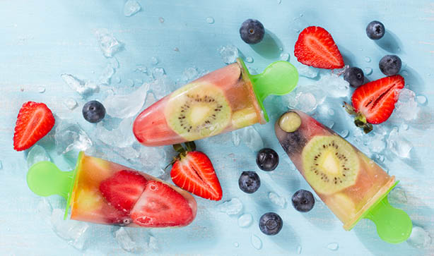 Three fruit ice lollies with strawberries, kiwis, blackberries, blueberries and ice