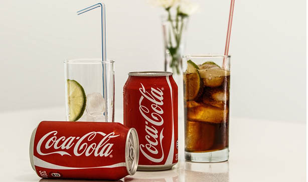 Coca - Cola cans and soda in two glasses