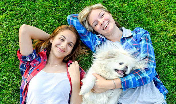 Two women smiling with their dog on the grass