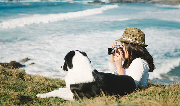 A hipster woman takes photos of her holiday spot with her dog on an old vintage camera