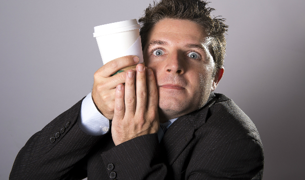 An anxious man clinging on to a coffee cup