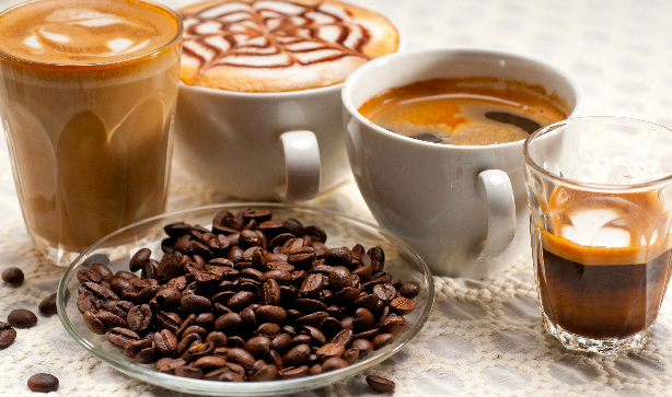 A selection of coffees, cappuccinos and lattes with a bowl of coffee beans