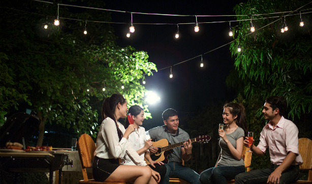 5 friends relaxing in a garden party with some drinks and a guitar in the evening