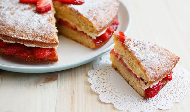 A slice of Victoria sponge cake on a plate next to a cake with the buttercream and jam filling showing
