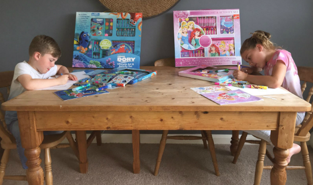 a boy and a girl sat at a table colouring with Disney Art Kits