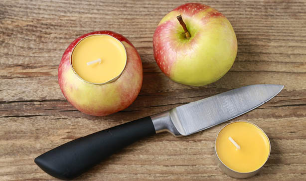 tea light candle in apple with a knife