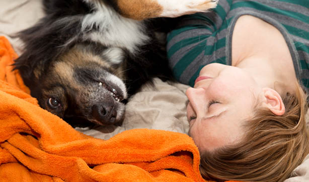 Woman lays next to dog