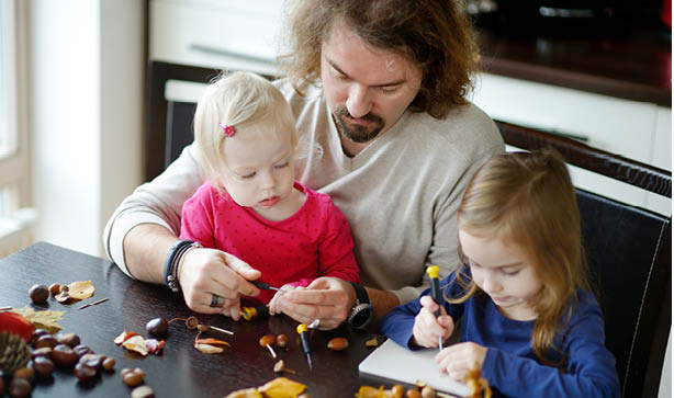 A dad with kids making arts and crafts with conkers
