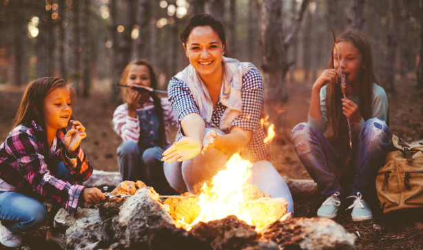 A family around a bonfire in the woods